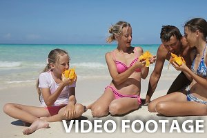 family on the beach eating mango