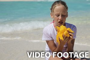 Young girl on the beach eating mango