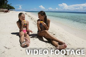 girls on the beach eating mango