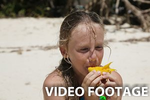 girl on the beach eating mango