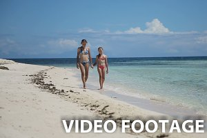 Two girls walking on beach
