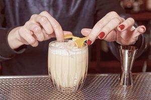 Female bartender is adding orange