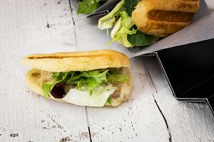 Sandwich with salad on wooden table