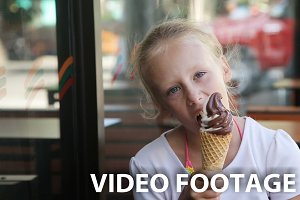 Young girl eating ice cream outdoors