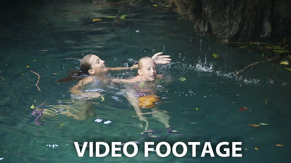 Young girl swimming in a waterfall