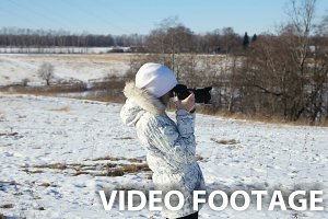Girl in winter park with camera