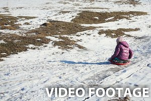 Little girl sledging down hill