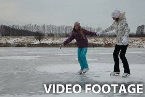girls ice skating on frozen lake