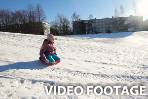 Yong girl sledging down hill