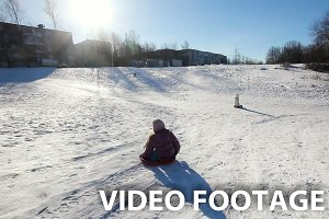 Young girls sledging down hill