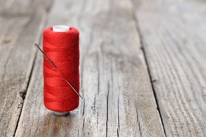 Spool of red thread with needle