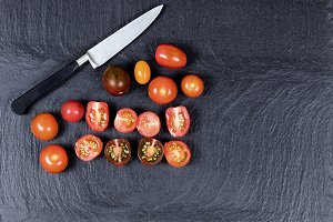 Knife and tomatoes on slate stone