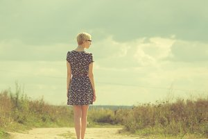 girl in a dress walking in a field