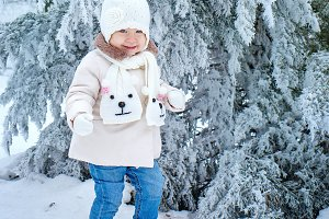 Child walking in winter forest