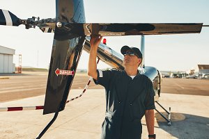 Male pilot examining helicopter