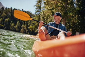 Mature man paddling a kayak