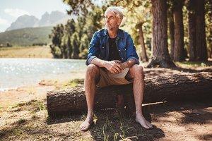 Senior man sitting on a log