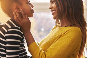 Black woman caressing her daughter