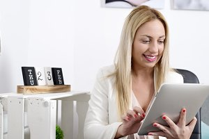 Attractive blonde woman using tablet