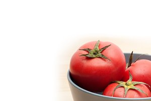 fresh ripe tomatoes on a blue bowl