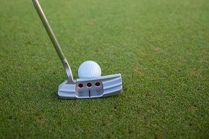Golf Ball on Green with Putter