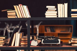 Books and typewriter on wooden shelfs