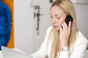 Attractive woman talking on the phone in front of computer. Business.