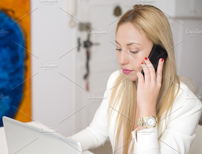Attractive woman talking on the phone in front of computer. Business. - Technology