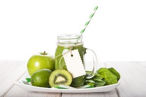 Green smoothie on a white wooden background