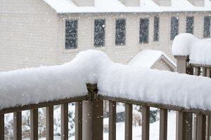 Snow piling high on deck rail