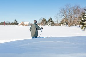 Senior man looks at snow driveway