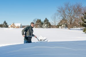 Senior man digs out driveway in snow