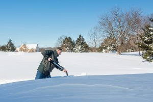 Senior male digs out driveway snow