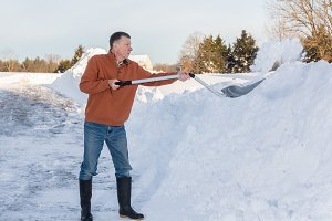 Old man digs out driveway in snow