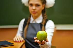 Student holding a green apple.