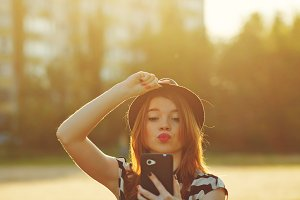 Girl in hat make Selfie. Kiss