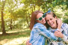 Happy women embracing and having fun over nature background
