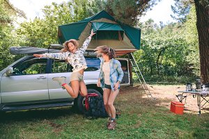 Young women having fun in campsite with 4x4 on background