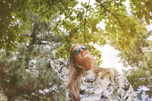 Woman with sunglasses touching over nature background