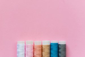 thread spools with pink background