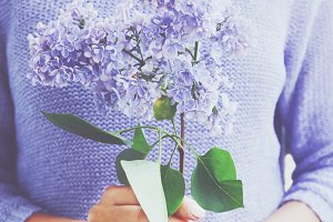 Girl holding branch of lilac