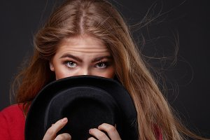 Woman hides her face behind hat