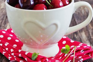 ripe cherries in a mug with a heart