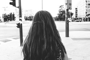 Back of a teen woman in a street