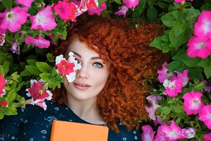 Red-haired Girl lies in flowers.