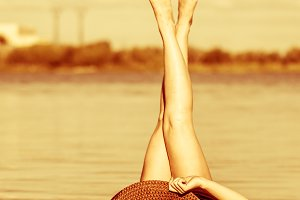 Girl in hat lying on beach.