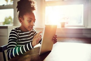 Afro-American Girl Surfing Internet Using Tablet