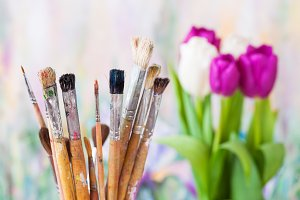 Paintbrushes and bouquet of tulips