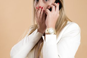 Attractive young blonde woman talking on the phone and is surprised