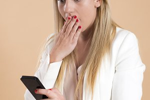 Attractive young blond woman uses the smartphone and is surprised